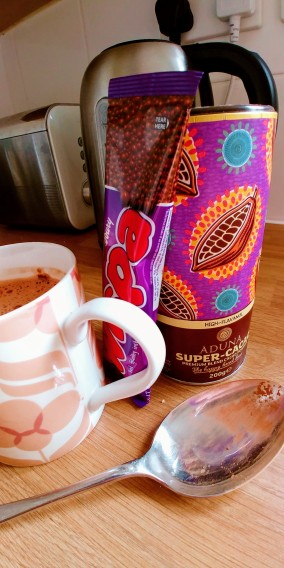 Photograph of cacao, hot chocolate sachet, and tablespoon